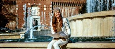 Lächelnde Frau nahe Sforza ziehen sich in Mailand, Italien mit Karte zurück lizenzfreie stockbilder