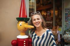 Lächelnde Frau nahe touristischem Souvenirladen in Pisa, Italien lizenzfreie stockfotos