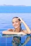 Lächelnde Frau reflektiert im Pool Stockfotografie