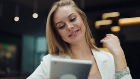 Lächelnde Frau repariert ihr Haar, das in einem Einkaufszentrum und im Ablesen einer Tablette sitzt stock footage