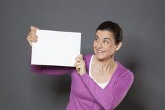Lächelnde Frau 30s des Spaßes, die eine Mitteilung macht, wenn ein weißer Einsatz vor ihr angehoben wird Stockbild