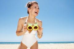 Lächelnde Frau am sandigen Strand, der flippige Ananasgläser hält Stockfotografie