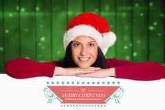 Lächelnde Frau in Sankt-Hut, der auf Plakat mit Weihnachtsgrüßen sich lehnt Lizenzfreies Stockbild