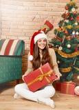 Lächelnde Frau in Sankt-Hut mit der Geschenkbox, die unter Weihnachtsbaum sitzt Lizenzfreies Stockfoto