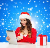 Lächelnde Frau in Sankt-Hut mit Geschenk- und Tabletten-PC Stockfotografie