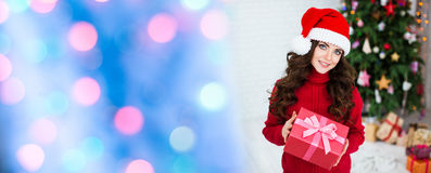 Lächelnde Frau in Sankt-Hut mit Geschenkbox Abstraktes Hintergrundmuster der weißen Sterne auf dunkelroter Auslegung Lizenzfreies Stockbild