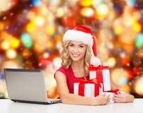 Lächelnde Frau in Sankt-Hut mit Geschenken und Laptop Stockbild