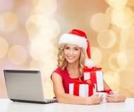 Lächelnde Frau in Sankt-Hut mit Geschenken und Laptop Lizenzfreie Stockbilder