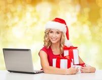 Lächelnde Frau in Sankt-Hut mit Geschenken und Laptop Stockfotografie