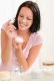 Lächelnde Frau setzte Feuchtigkeitscremesahne auf Wekzeugspritze Lizenzfreie Stockfotos