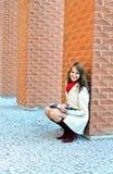 Lächelnde Frau sitzt und liest ein Buch Lizenzfreies Stockfoto