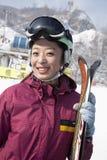Lächelnde Frau in Ski Resort, der Skis hält Stockfotos