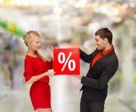 Lächelnde Frau und Mann mit rotem Prozentverkauf unterzeichnen Stockbilder