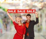 Lächelnde Frau und Mann mit rotem Verkauf unterzeichnen Stockbilder