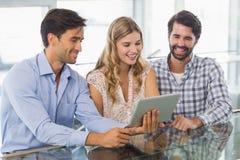 Lächelnde Frau und zwei Männer, die digitale Tablette verwenden Stockfotografie