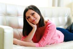 Lächelnde Frau von mittlerem Alter, die auf dem Sofa liegt Lizenzfreie Stockfotos