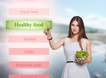 Lächelnde Frau wählen gesundes Lebensmittel auf futuristischem Schirm Lizenzfreies Stockfoto