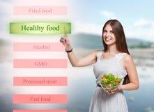 Lächelnde Frau wählen gesundes Lebensmittel auf futuristischem Schirm Stockbilder
