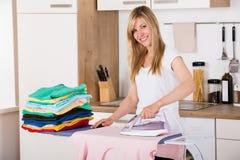 Lächelnde Frauen-bügelnde Kleidung mit elektrischem Eisen lizenzfreies stockbild