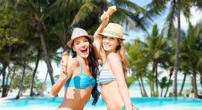 Lächelnde Frauen, die Eiscreme auf Strand essen Stockfotos