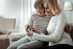 Lächelnde Frauen, die Foto ihres Kindes im Mutterleib überprüfen lizenzfreie stockfotos