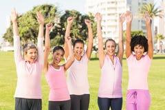 Lächelnde Frauen, die Rosa für das Brustkrebs und Zujubeln tragen lizenzfreies stockfoto