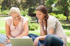 Lächelnde Frauen mit einem Laptop Stockbild