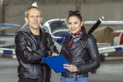 Lächelnde Frauen-und Mann-Piloten in einem Hangar lizenzfreie stockfotografie