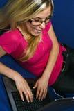 Lächelnde Frauenarten auf Laptop Stockfotos