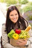 Lächelnde Fraueneinkaufsgemüse-Lebensmittelgeschäft-Papiertüte lizenzfreies stockbild