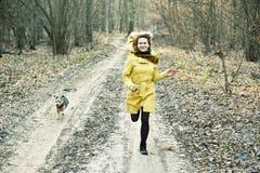 Lächelnde Frauenläufe mit Hund im Wald Lizenzfreie Stockfotografie