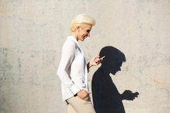 Lächelnde Frauenlesetextnachricht am Handy Stockfotos