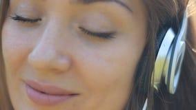 Lächelnde Frauennahaufnahme in hörender Musik der Kopfhörer Das Mädchen, das ein Lied mit ihren Augen lächelt und genießt, schlos stock video footage