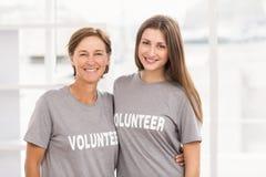 Lächelnde Fraufreiwillige, die Arme um einander setzen lizenzfreies stockfoto