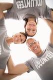 Lächelnde Freiwillige, die unten zur Kamera schauen Stockbild