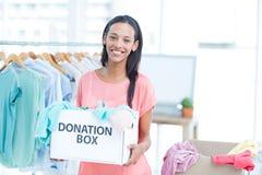 Lächelnde freiwillige Holding ein Kasten Spenden Lizenzfreies Stockfoto