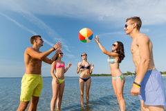 Lächelnde Freunde in der Sonnenbrille auf Sommerstrand Lizenzfreie Stockfotografie