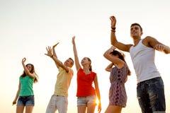 Lächelnde Freunde, die auf Sommerstrand tanzen Stockfoto