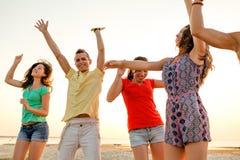 Lächelnde Freunde, die auf Sommerstrand tanzen Stockfotografie