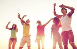 Lächelnde Freunde, die auf Sommerstrand tanzen Stockfotos