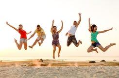 Lächelnde Freunde, die auf Strand tanzen und springen Stockbild