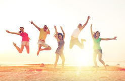 Lächelnde Freunde, die auf Strand tanzen und springen Lizenzfreies Stockfoto
