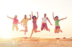 Lächelnde Freunde, die auf Strand tanzen und springen stockfotografie