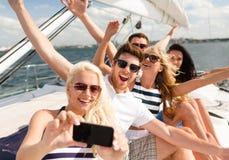 Lächelnde Freunde, die auf Yachtplattform sitzen Stockbilder