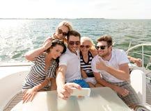Lächelnde Freunde, die auf Yachtplattform sitzen Lizenzfreie Stockfotografie