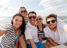 Lächelnde Freunde, die auf Yachtplattform sitzen Stockfotos