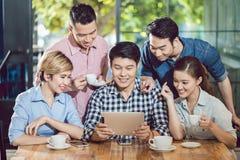 Lächelnde Freunde, die digitale Tablette im Café betrachten lizenzfreie stockfotos