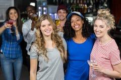 Lächelnde Freunde, die etwas trinken Lizenzfreie Stockbilder