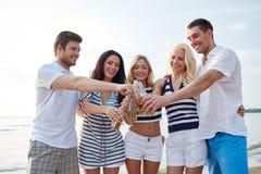 Lächelnde Freunde, die Flaschen auf Strand klirren lizenzfreies stockfoto