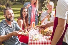 Lächelnde Freunde, die gegrilltes Lebensmittel während der Geburtstagsfeier im Garten essen lizenzfreie stockfotos